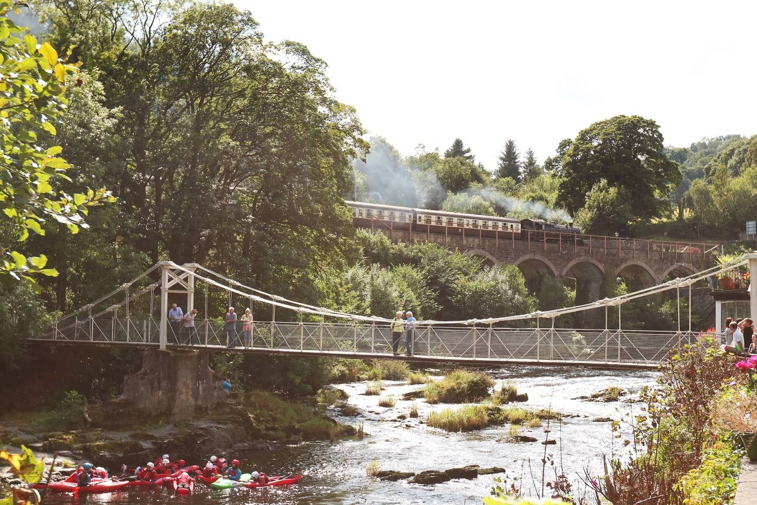 A photograph of chain bridge with a steam train in the background