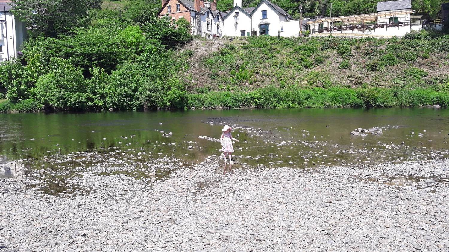 A photograph of a little girl paddling in a river in front of a pub